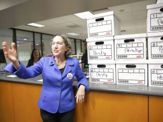 Michele Dauber, standing at the counter of the Registrar of Voters in San Jose on Jan. 11, gestures to supporters after handing over boxes containing signatures to place the recall of Santa Clara County Judge Aaron Persky on the June ballot.