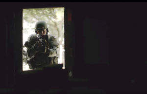 Police officers in SWAT uniforms burst into a darkened building in a police recruitment video.