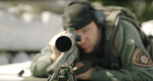 A police officer aims a rifle in a recruitment video.