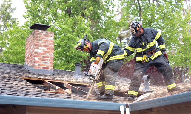 Firefighters from San Mateo Truck 21 cut a ventilation hole to help access an attic fire in a Menlo Park home Saturday evening. Photo by Peter Mootz.