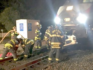 Menlo Park firefighters work to remove a 1950s-era Austin Healey convertible from the front of a Caltrain at the Watkins Avenue crossing Saturday night. Photo provided by the Menlo Park Fire Protection District.