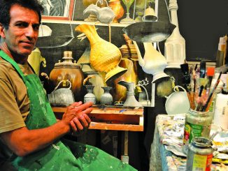 """Artist Hadi Aghaee poses with his realistic acrylic painting titled """"Remnant of the Coppersmith Bazaar."""" He will show his art this weekend in Palo Alto."""