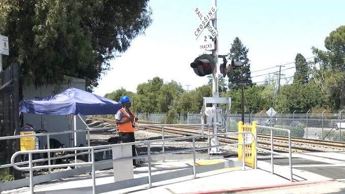 ON DUTY — A Cypress Security guard keeps an eye on the Caltrain crossing at Charleston Road in Palo Alto. Post file photo.