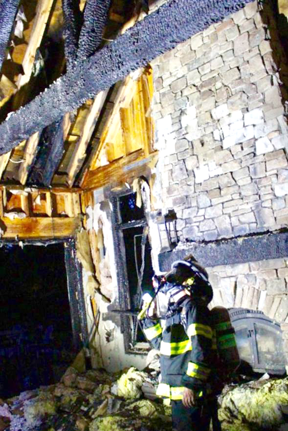 Menlo Park Fire Investigator David Perrone inspects  damage in the inside a home at 11 Robert S Drive. Photo by Peter Mootz.