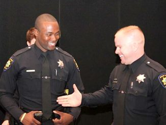 Tom DeStefano, right, puts his hand out to former Palo Alto police officer Marcus Barbour in this 2014 photo posted on social media by the Palo Alto Police Department.