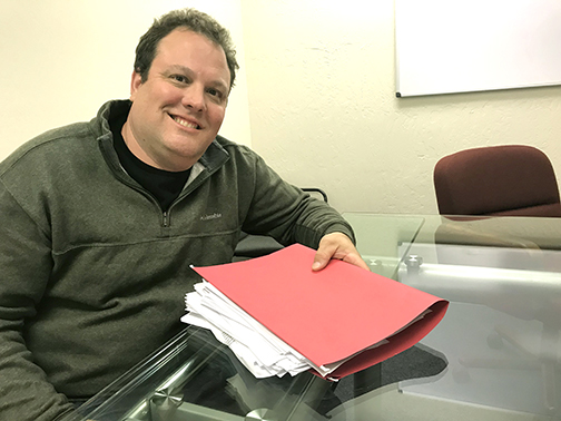 Mark Dinan holds a file folder of public documents he obtained detailing the East Palo Alto Sanitary District's spending on travel. Post photo.